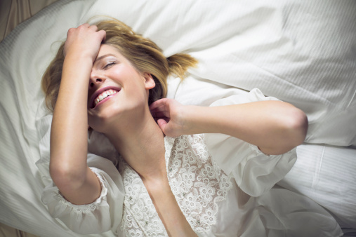 Young woman lying on bed with hand in hair