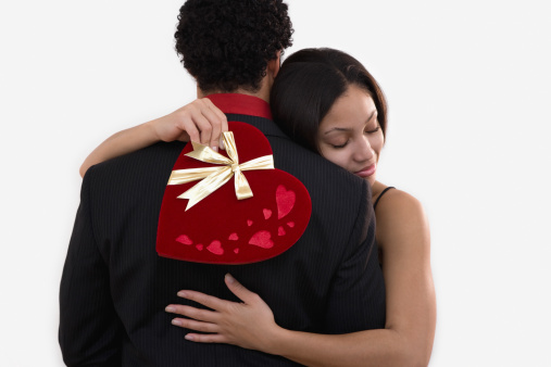 African woman holding valentines gift and hugging boyfriend